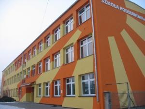 zdjęcie przedstawiające front oraz boczną ścianę budynku przy ulicy Rolnej pomalowanego we wzór przedstawiający promienie słońca w kolorach żółtym i pomarańczowym