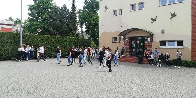 Grupa uczennic klas VII i VIII podczas występu tanecznego na tle wejścia do szkoły