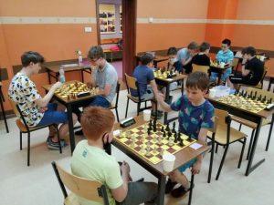 uczniowie przy szachownicach podczas rozgrywki; na pierwszym planie uczniowie klasy piątej