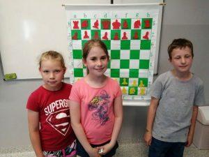 uczniowie klas młodszych na tle tablicy z polem szachowym