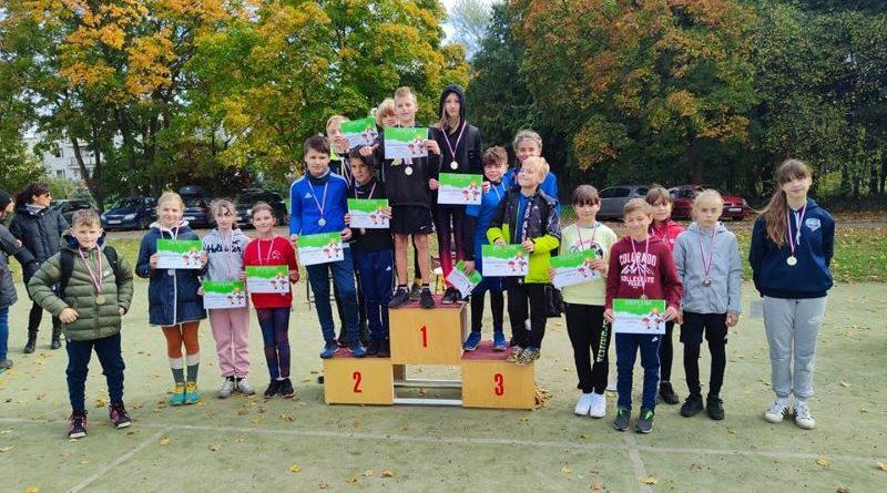 na zdjęciu grupa uczniów stojąca na i obok podium stanowiąca medalistów wszystkich kategorii wiekowych biorących udział w zawodach. W tym uczniowie SP Czerwonak.